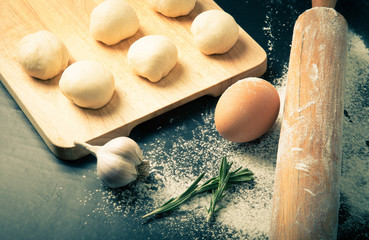 Garlic, rosmary, egg, rolling pin and pieces of dough on the woo