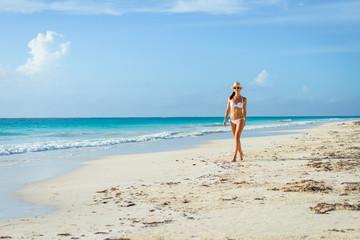 Sexy tanned woman in bikini on tropical natural beach