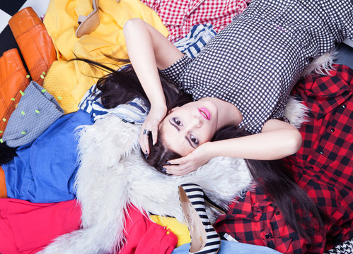 Stressed young woman lying down on a pile of clothes