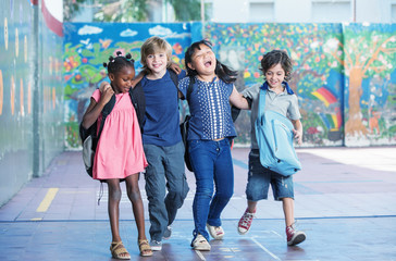 Happy kids embracing and smiling in the elementary schoolyard. I