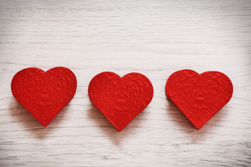 valentines day background with three hearts on wooden background