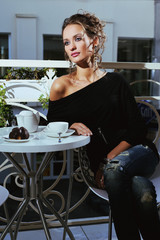 Fashion young woman sitting in cafe and eating cake