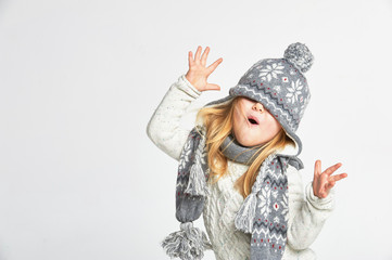 Beautiful blond girl playing in the winter warm hat and scarf on