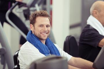 lächelnder mann trainiert im sportstudio