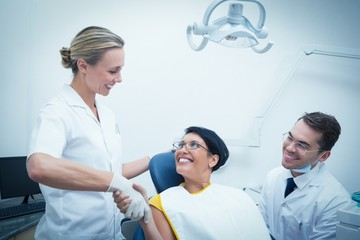 Female dentist shaking hands with woman