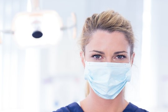 Portrait of a dentist in mask looking at camera