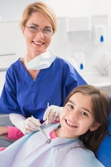 Smiling pediatric dentist with a happy young patient