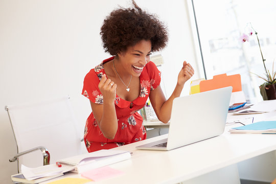 Excited Woman Working At Desk In Design Studio