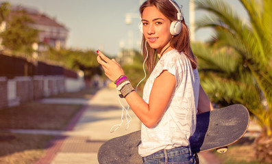 Young girl with skateboard and headphones listening music