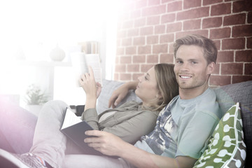 Young couple reading book in sofa