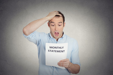 shocked looking man disgusted at corporate monthly statement