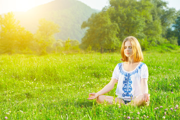 Wall Mural - young woman doing yoga on green grass
