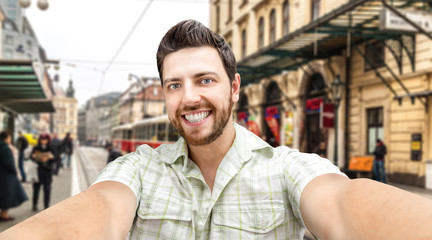 Happy young man taking a selfie photo in Prague, Czech Republic.