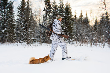 hunter walking on the skis with dog