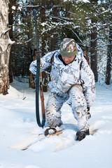 hunter with gun puts on skis