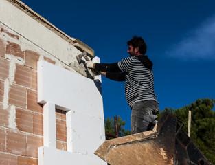 worker mounts sheets of polystyrene on external vertical walls