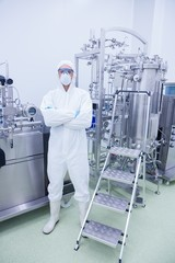 Scientist in protective suit standing with arms crossed