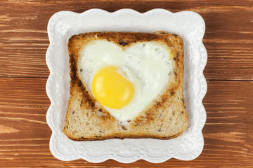 Slice of cereal toast bread with cut out heart shape full egg on