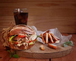 Hamburger with fries and a drink on the wooden