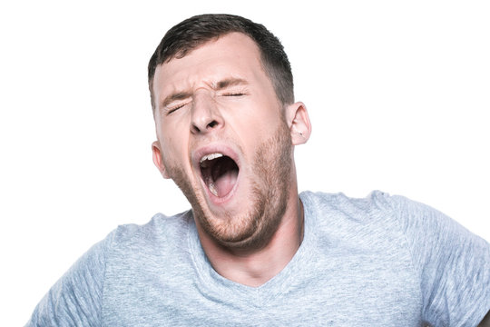 Tired sleepy young man yawning