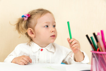 Cute child girl drawing in preschool at table in kindergarten