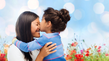 happy little girl hugging and kissing her mother