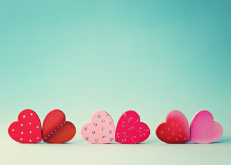 Six hand-painted wood hearts over blue background