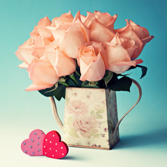 Pink roses in a vase and vintage wood hearts