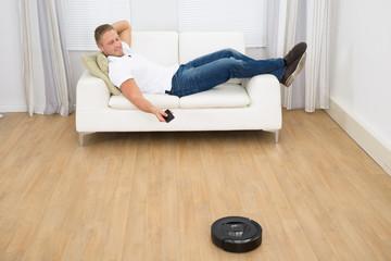 Man Using Robotic Vacuum Cleaner Remote Control