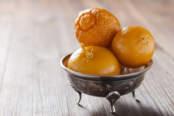 Moroccan pickled lemons in a metal bowl on a wooden background