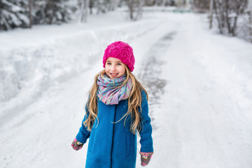 Portrait of a little girl dressed in a blue coat and a pink hat