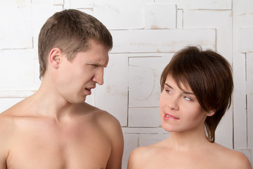 Young couple flirting near the white wall