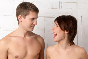 Young couple with emotions of giggle near the white wall