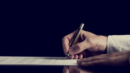 Signing a contract over dark background