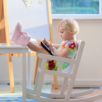 Little girl using tablet pc at home