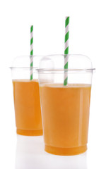 Orange juice in fast food closed cups with tubes isolated