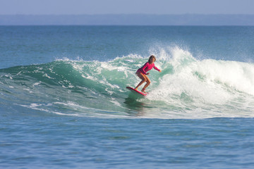 Surfer girl on the wave, Indonesia.