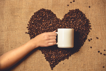 Toned photo of person holding white mug against heart of coffee