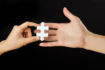 黒い背景で白いパズルのピースを持っている人間の手