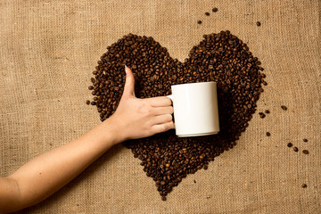 photo of woman holding mug against heart made of coffee beans