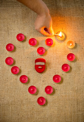 photo of person lighting up candles in shape of heart