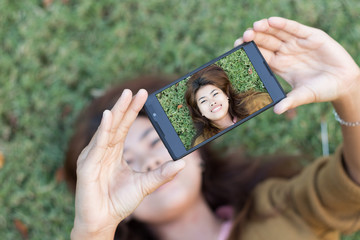 young women use smartphone self picture selfie on green grass