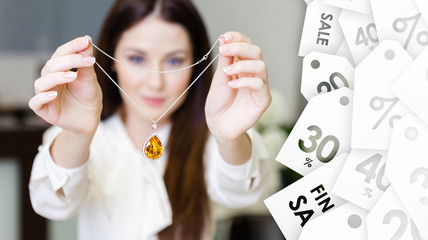 Woman keeping necklace with yellow sapphire at jeweler's shop. Special offer. Concept of wealth and luxurious life