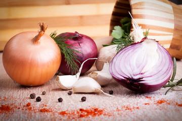 close up of garlic, onion fresh herbs on  wooden board