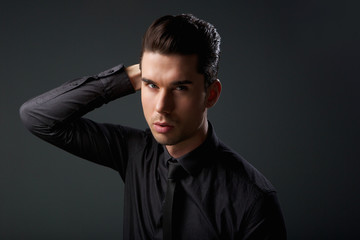 Portrait of a stylish young man with hand in hair