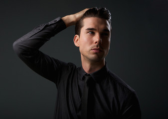 Attractive young man with hand in hair