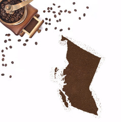 Coffee powder in the shape of British Columbia and a coffee mill