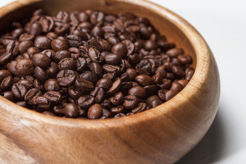 Many coffee beans in wooden bowl