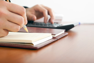 Businessman using a calculator on a wooden desk.