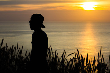 A man standing at sunset at the seaside